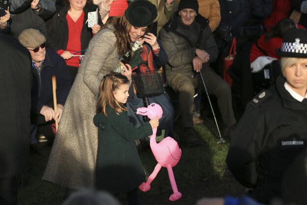 Kate, vojvodkyňa z Cambridge sa rozpráva s princeznou Charlotte, ktorá si drží darček - ružového plameniaka - počas príchodu na tradičnú rannú vianočnú bohoslužbu v obci Sandringham v anglickom grófstve Norfolk 25. decembra 2019.