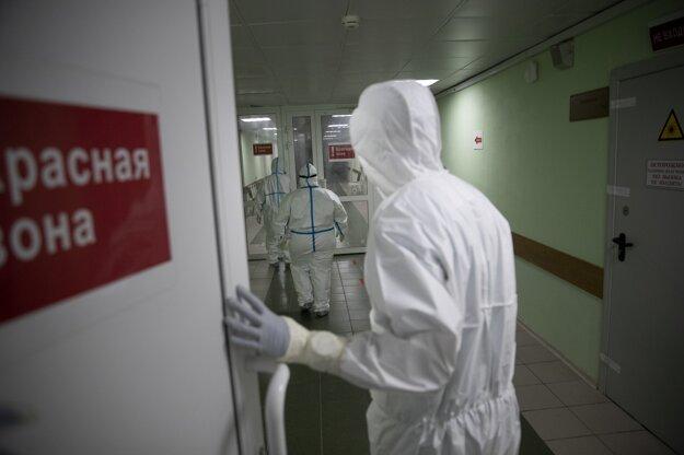 Zdravotný personál v špeciálnych ochranných odevoch kráča chodbou v červenej zóne na jednotke intenzívnej starostlivosti v nemocnici v Moskve.
