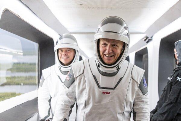 Doug Hurley (v popredí) a Bob Behnken kráčajú cez mostík do kapsule Crew Dragon.