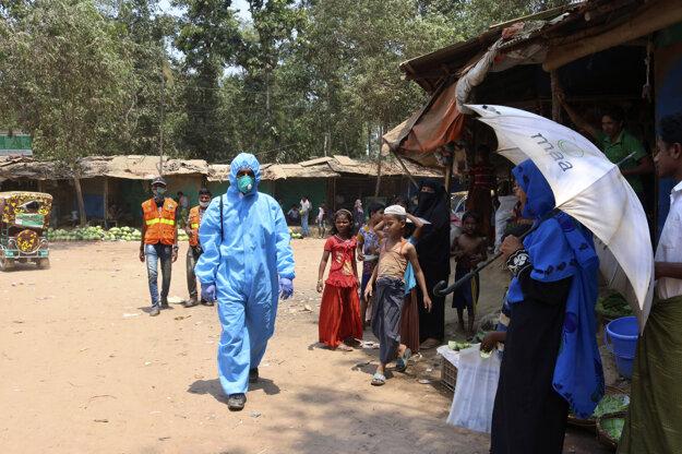 Zdravotník v ochrannom obleku kráča v utetečencom tábore Kutupalong v bangladéšskom okrese Cox's Bazar.