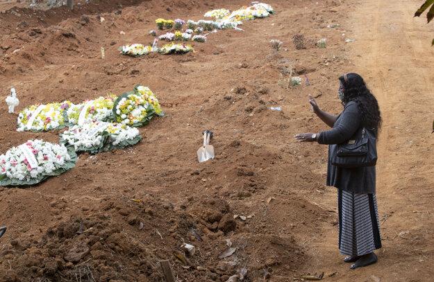 Vera Lucia Souzová sa modlí na mieste, kde pochovali jej brata Paula Roberta da Silvu, ktorý zomrel na následky ochorenia COVID-19. Brazília má aktuálne už tretí najvyšší počet obetí koronavírusu na svete.