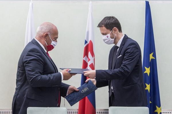 Minister financií SR Eduard Heger (vpravo) a minister financií Poľskej republiky Tadeusz Kościński si vymieňajú dokumenty po podpise memoranda o spolupráci v oblasti boja s daňovými únikmi.