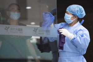 Žena čistí sklenené dvere zdravotného strediska na testovanie COVID-19 v Pekingu.