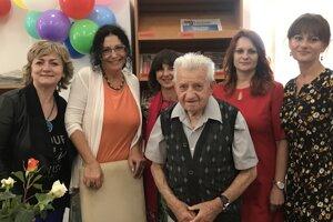 Oslávenec Ján Slávik počas oslavy medzi dámami z knižnice.