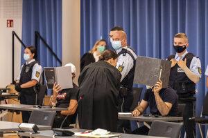 Obvinení muži si zakrývajú tváre v súdnej miestnosti vo Freiburgu.
