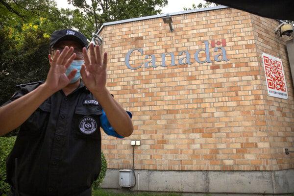 Policajt pred kanadskou ambasádou v Pekingu.