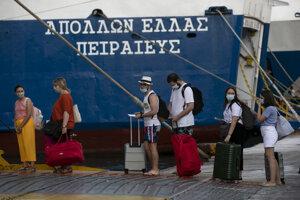 Cestujúci s rúškami čakajú v rade na trajekt, ktorý smeruje na grécke ostrovy v Egejskom mori v gréckom prístave Pireus pri Aténach v sobotu 1. augusta 2020.