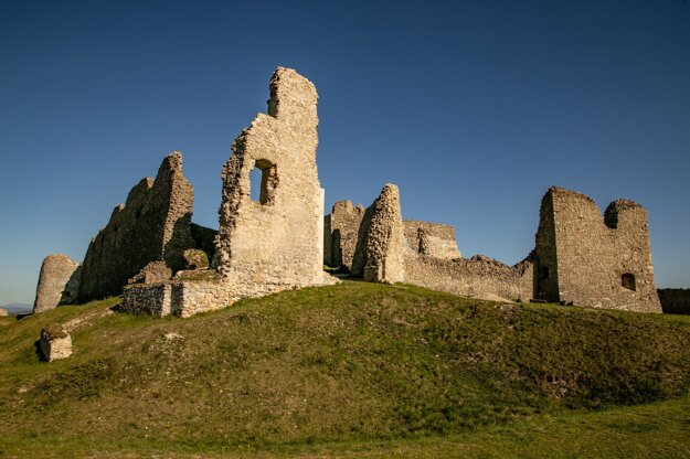Klesajúce slnko ponad zrúcaninu hradu Branč z roku 1317 na jar, Podbranč