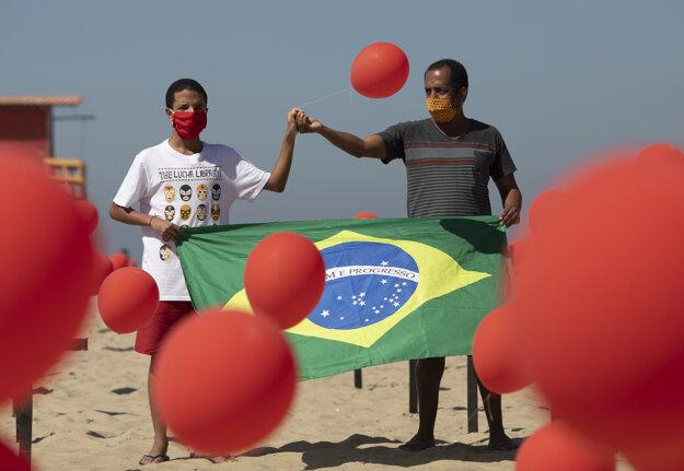 Marcio Antonio do Nascimento (vpravo) a Lucas Cruz, otec a brat 25-ročného Huga do Nascimenta, ktorý podľahol nákaze koronavírusom, držia v rukách brazílsku vlajku na počesť všetkým obetiam ochorenia Covid-19.