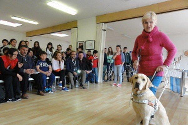 Nevidiaca Iveta predvádza vodiaceho psa pred tureckými školákmi.