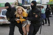 Policajti zadržiavajú jednu z účastníčok protestov.