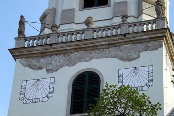 Poškodená fasáda pod balustrádou.
