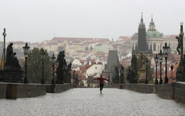 Muž beží cez prázdny Karlov most v Prahe v stredu 14. októbra 2020.