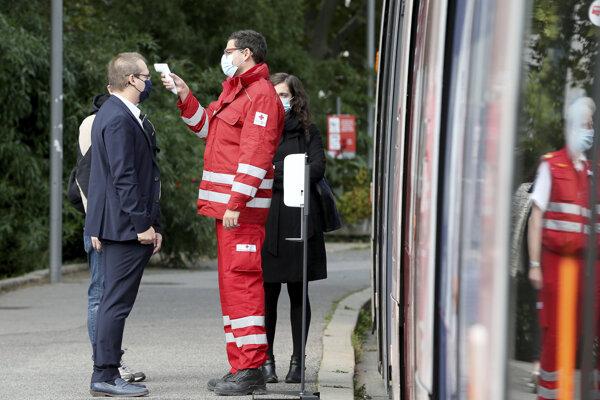 Zdravotník kontroluje telesnú teplotu na električkovej zastávke vo Viedni.