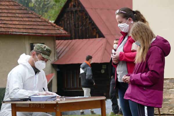 Otestované obyvateľky čakajú na certifikát s výsledok antigénového testu počas pilotnej fázy celoplošného testovania na ochorenie COVID-19 v obci Zázrivá.
