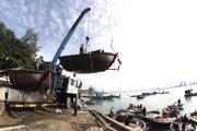 Ľudia premiestňujú rybárske lode do bezpečia v oblasti Danang vo Vietname.