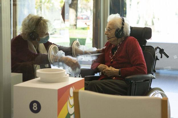 Žena sa dotýka príbuznej cez otvory na ruky na plexiskle v domove dôchodcov počas koronavírusovej pandémie v severotalianskom meste Castelfranco Veneto.
