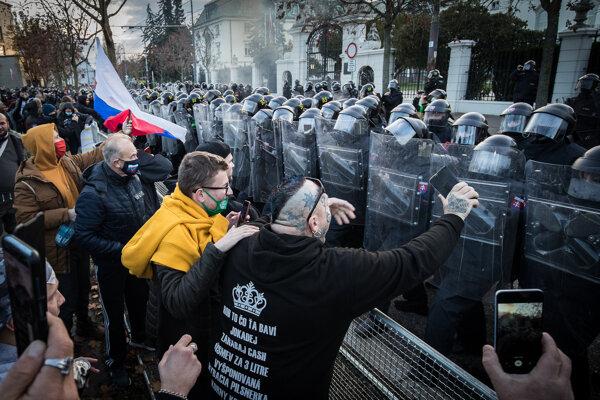 Demonštranti a policajti počas nepovoleného protivládneho protestu pred Úradom vlády.