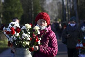 Žena s kvetmi na pohrebe aktivistu Ramana Bandarenku v Minsku.