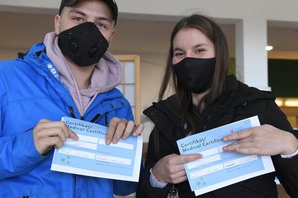Mladý pár ukazuje negatívny certifikát po testovaní v obci Valaliky.
