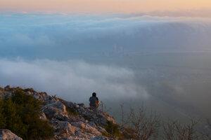Turista na okraji Zádielskej planiny pri západe slnka, dole obec Dvorníky, cementáreň pri Turni nad Bodvou, hmla sa prevaľuje cez planinu Dolný vrch.