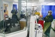 Zdravotníci v ochranných odevoch pracujú na Jednotke intenzívnej starostlivosti.