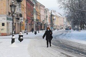 Žena kráča po zasneženej Hlavnej ulici v Košiciach.