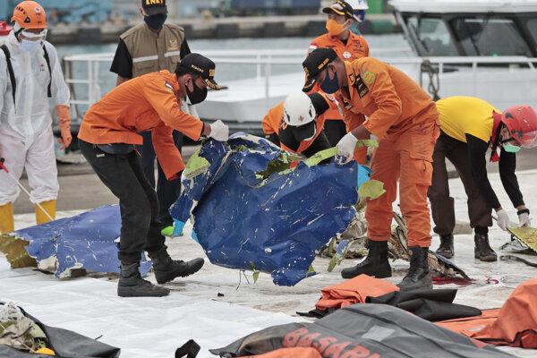 Pracovníci zhromažďujú časti havarovaného indonézskeho lietadla.