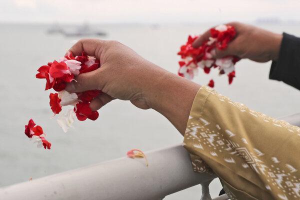 Smútiace rodiny hádzali z paluby lode na vodu červené lupene.