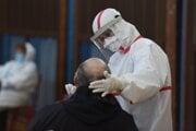 Zdravotníčka v ochrannom odeve odoberá vzorku počas testovania na COVID-19 v telocvični na Základnej škole s materskou školu na Námestí učeného tovarišstva v Trnave
