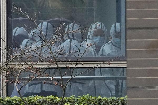 Členovia vyšetrovacieho tímu svetovej zdravotníckej organizácie (WHO) v ochrannom oblečení počas návštevy Centra pre prevenciu a kontrolu chorôb zvierat v meste Wu-chan.