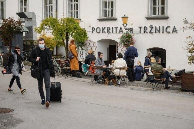 Ľudia sedia pred tržnicou v slovinskej metropole Ľubľana v piatok 16. októbra 2020.