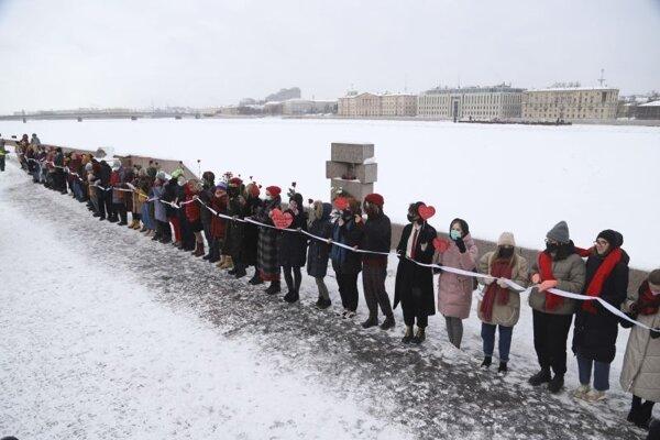 Ženy s ochrannými rúškami vytvorili vytvorili ľudskú reťaz na prejav solidarity s tými, ktorí boli zadržaní počas protestov požadujúcich prepustenie uväzneného vodcu ruskej opozície Alexeja Navaľného v Petrohrade v nedeľu 14. februára 2021.
