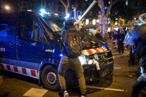 Demonštrant rozbíja policajné auto počas kolízie s polícou po proteste v Madride v reakcii na utorkové zatknutie rapera Pabla Haséla, odsúdeného za urážku monarchie.