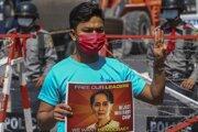 Protivládny demonštrant gestikuluje pred policajnou barikádou počas protestu proti vojenskej okupácii, v mjanmarskom meste Mandalay 24. februára 2021. Proti prevratu v krajine už tretí týždeň prebiehajú masové demonštrácie. Protestujúci žiadajú návrat civilnej vlády a tiež prepustenie Aun Schan Su Ťij.