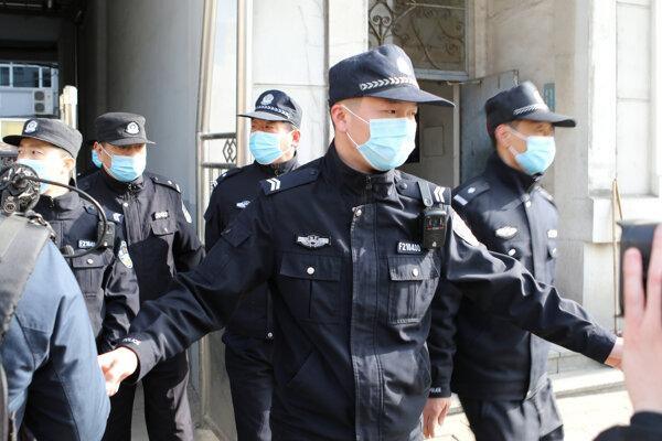 Čínski policajti hliadkujú pred budovou súdu, kde priviedli obvineného kanadského podnikateľa Michaela Spavora.