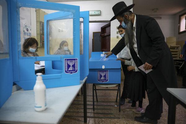 Ultraortodoxný žid odovzdáva svoj hlas vo volebnej miestnosti v meste Bnei Brak počas parlamentných volieb v Izraeli v utorok 23. marca 2021.