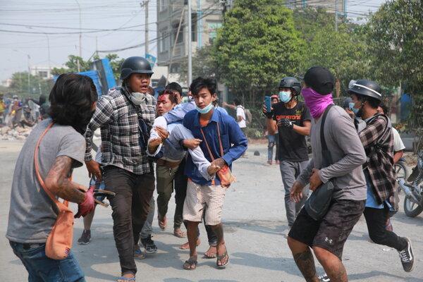 Protivládni demonštranti nesú na rukách muža so zranením hlavy počas protestu proti vojenskej okupácii, v mjanmarskom meste Mandalay.