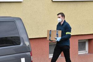 Policajti vynášali krabice so zaisteným materiálom.
