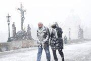 Chodci prechádzajú počas snehovej prehánky po Karlovom moste v Prahe 6. apríla 2021.
