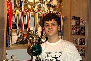 """""""Krasokorčuľovanie je život. To ostatné sú len detaily,"""" hovorí slogan na jeho tričku. Simon pózuje pred časťou svojich trofejí. Ďalšie víťazné poháre sú umiestnené v školských vitrínach."""