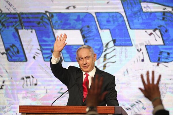 Izraelský premiér Benjamin Netanjahu máva svojim podporovateľom po zverejnení prvých odhadov v predčasných parlamentných voľbách v Izraeli v centrále jeho strany Jednota (Likud) v  Jeruzaleme v utorok 23. marca 2021.