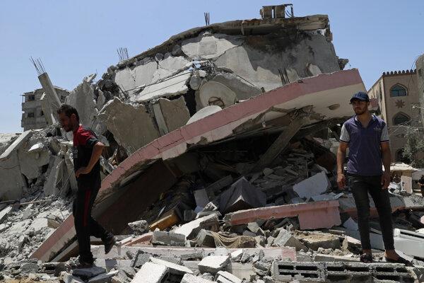 Ľudia stoja pri troskách budovy zničenej raketou v pásme Gazy.