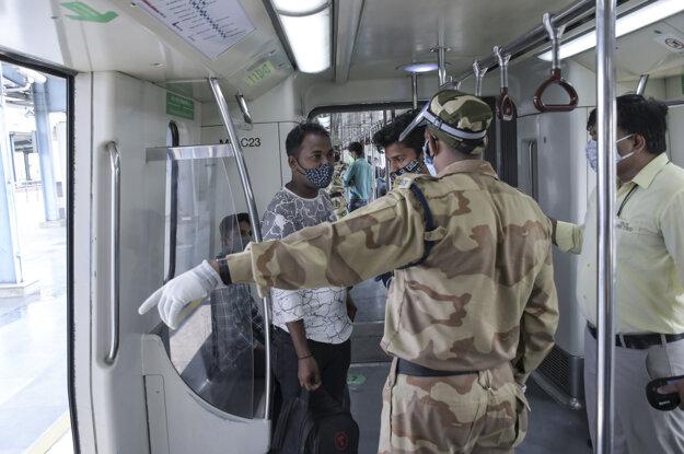 Strážnik vykazuje pasažiera zo súpravy metra v indickom Naí Dillí.