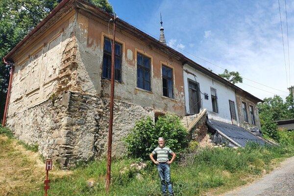 Ladislav Hedvigi pred chátrajúcou budovou bývalej školy v Kyjaticiach.