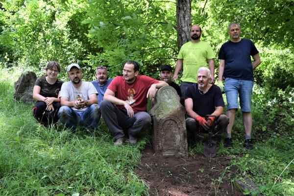 Brigádnici v Hornom Tisovníku pri náhrobníku, ktorý museli vykopať a premiestniť.