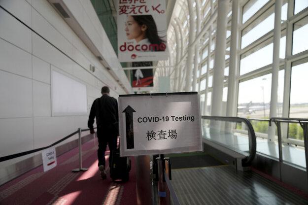 Tabuľa s nápisom testovanie na ochorenie COVID-19 na letisku v Tokiu.