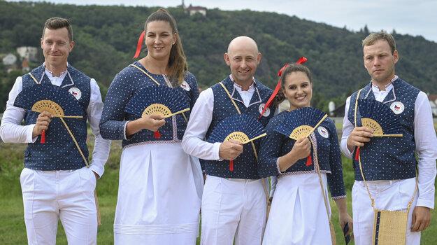 Českí športovci pózujú v olympijskom oblečení.