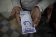 Na archívnej snímke zo 16. marca 2012 žena ukazuje novú venezuelskú bankovku v hodnote 500-tisíc bolívarov v Caracase