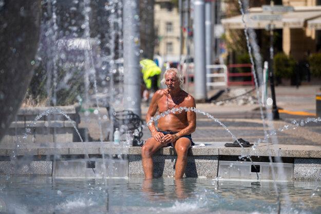 Muž sa ochladzuje vo fontáne pred Prezidentským palácom v Bratislave v júli 2021.